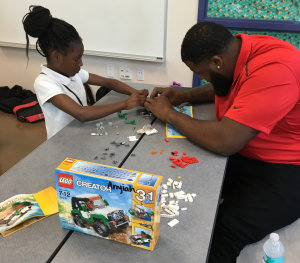 Tampa Bay Buccaneers' Donovan Smith works with a Tampa., Fla., elementary school student on a Lego project.